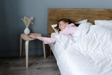 Sleepy Woman Turning Off Alarm On Mobile Phone
