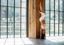 Pregnant Female Doing Handstand In Studio
