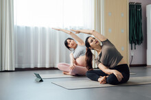 Pregnant Woman And Friend Doing Yoga