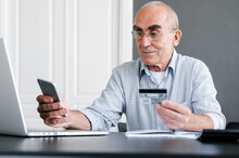 Senior Man Paying Online With Smartphone And Credit Card