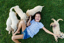 Little Girl Enjoys Playing With Her Puppies