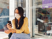 Young Woman Sitting On The Bus Stop Looking At Her Phone