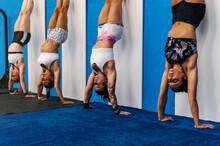 Sportswomen Doing Handstand Near Wall