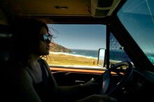 Young Woman Driving A Vintage Camper Van Though The Californian Coast.