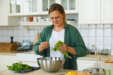 Middle Aged Woman Adding Lettuce To Salad