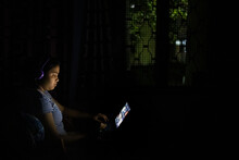 Teenage Girl Browsing Internet At Night In A Tablet
