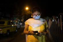 Indian Woman Wearing Mask And Browsing Smartphone In The Street Of Kolkata