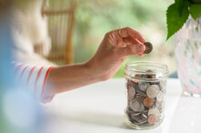 Putting A Coin In A Savings Jar