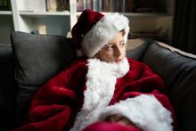 Boy In Santa Costume Looks Out Window