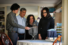 Hanukkah: Family Watches As Teen Lights Candles