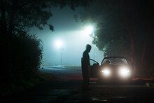 A Blurred Hooded Figure Standing In Front Of A Car At Night.