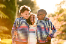 Three Children With Arms Around Each Other Laughing