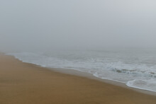 Ocean Waves Hitting The Beach Covered In Fog