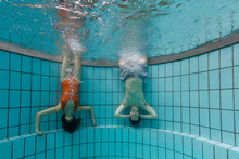 Two Friends Are Fooling Around In A Residential Pool, Letting Out Bubbles While Hanging Upside Down Along The Wall.