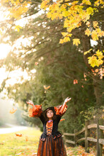 Girl In Orange Witch Costume Smiles At Falling Leaves