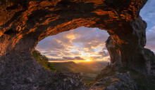 Woman Watching Sunset Under A Stone Arch