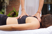 Woman Osteopath Hands On Patient's Back