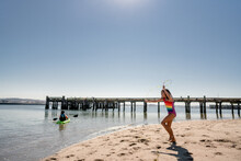 Wide Shot Of Girl Jumping Rope With Seaweed By Pier