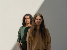Two People In Green And Brown Outfits Posing Creatively