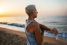 Serious Mature Sportswoman Warming Up On Seashore In Evening