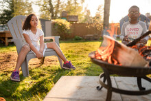 Siblings Sit Casually Staring Into Backyard Campfire