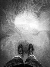 Man's Legs With A Sewer Flooded With Water.