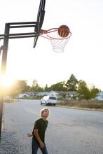 Boy Makes Basketball Shot In Neighborhood Hoop At Sunset