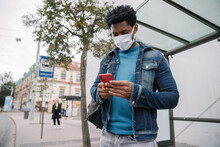 Man Using Cellphone At Bus Stop