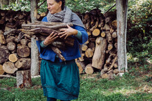 Mature Woman Carrying Wood For Burning