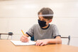 Boy with mask in a classroom