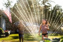 Young Girl With Undercut Runs Through Sprinkler