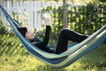 A Woman Using A Cellphone In An Outdoor Hammock