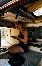 Wanderlust Girl Planing The Roadtrip With A Tablet Inside A Vintage Van.
