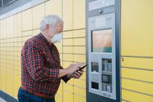 Senior Man Using Cellphone At Parcel Station