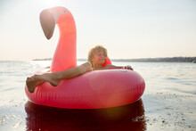 Smiling Boy Floats Peacefully In Pink Flamingo Floatie