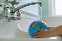 Child Washing Globe In Sink