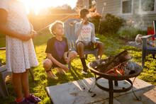 Siblings Roast Marshmallows By Backyard Campfire