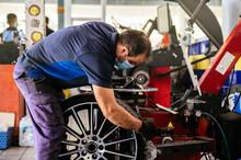 Male Technician Checking Wheel Near Colleagues