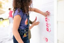 Girl Makes Red Paint Handprint On Garage Door