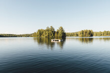 Landscape View Of A Lake With A Floating Pier On The Water In Front Of Trees