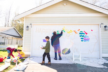 Black Dad And Three Children Paint Mural On House Garage Door