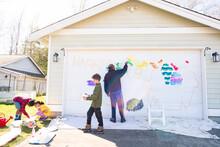 Black Dad And Three Children Paint Mural On House Garage Door