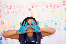 Girl Holds Up Blue Painted Hands