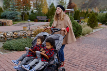 Mother With Two Twin Girls Family In A Large Stroller For Children