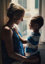 Mother And Son Playing By The Window In Their Room