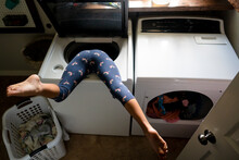Child Upside Down In Washing Machine With Legs Kicked Up