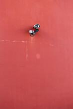 Security Camera Against A Red Wall