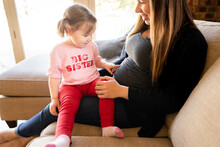 Cute Girl In Pink Big Sister Shirt Points To Mother's Pregnant Belly