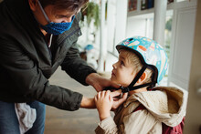 Dad Wearing A Mouth Mask Helping His Son Putting On His Bicycle Helmet