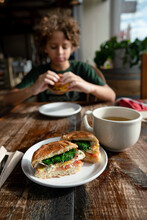 Breakfast Sandwich At Cafe Table Across From Eating Child